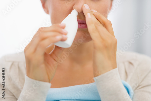 Closeup on young woman using nose drops