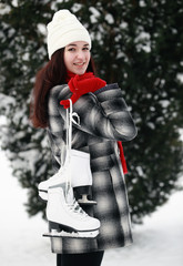 Beautiful young woman holding ice skate