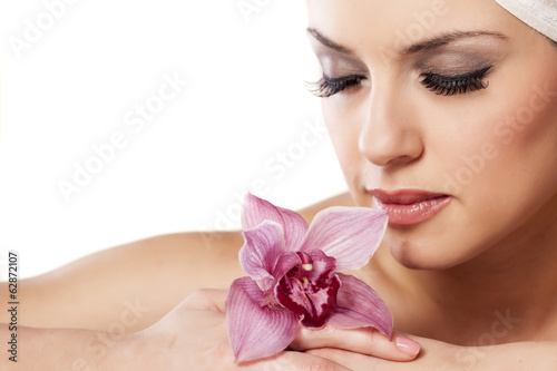 beautiful woman with a towel on her head posing with orchid