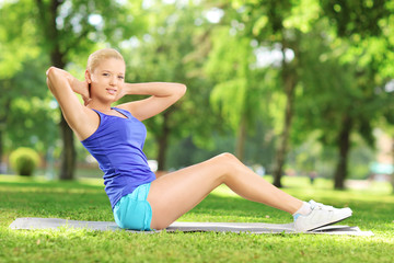 Young female doing exercises on mat in a park