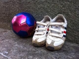 Scarpe e pallone di bimbo a riposo
