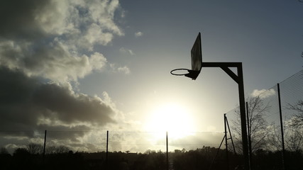 Beautiful time lapse of sun in the clouds on a basketball court