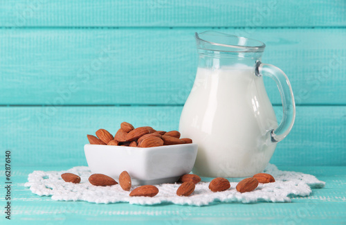 Almond milk in jug with almonds in bowl,