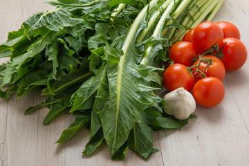 Cicoria catalogna, aglio e grappolo di pomodorini su un tavolo