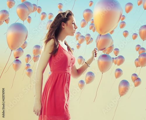 Young brunette woman among the balloons