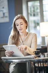 beautiful young woman sitting in a cafe and using a digital tabl