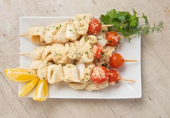 Spiedini di pesce crudi nel piatto ceramica bianco