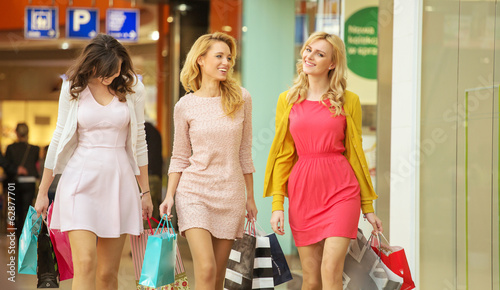 Three attractive girls walking around the shopping mall