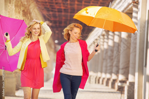 Self-confident girls walking with umbrellas