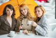 Three women, the coffee and the umbrella