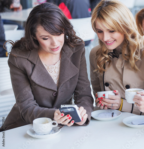 Cheerful women playing the mobile phone