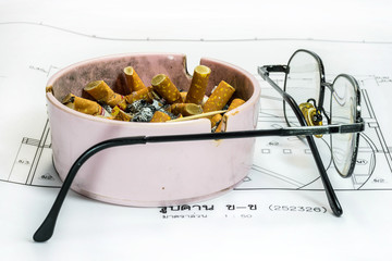 Ashtray and glasses on white blueprint background.