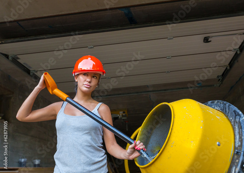 Pretty young woman builder and concrete mixer