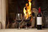 Copas de vino y bottela en frente del hogar, la chimenea, fuego.