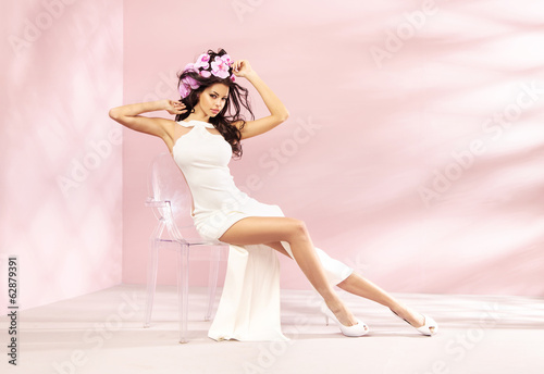 Shapely brunette girl sitting on the crystal chair
