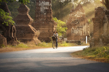 young lady riding bike in ancient city, thailand