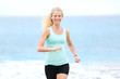 Running woman jogging outside on beach