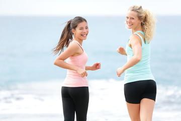 Running women jogging training on beach