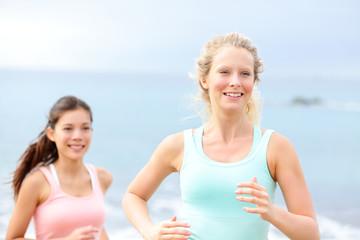 Running women - female runners on beach