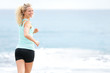 Woman running on beach looking back jogging