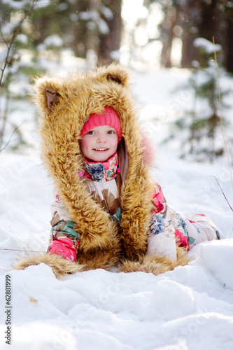 Funny girl in a fur hat in winter forest