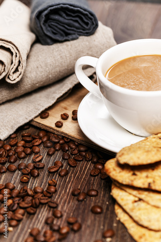 A cup of coffee with biscuits