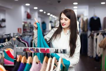 Young female buyer choosing sweater