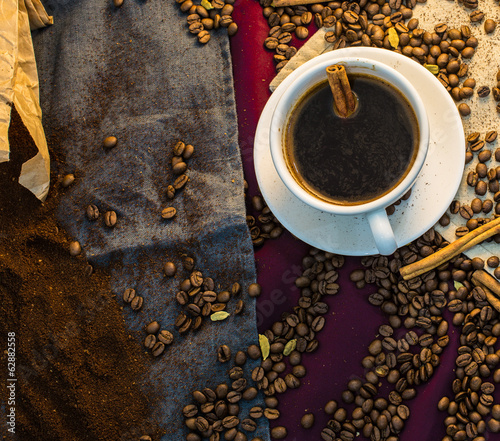 A cup of coffee and beans scattered on the table