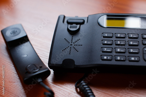 A black office phone with a cord