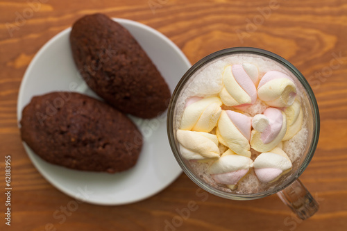 Cocoa with marshmallows and cakes on the table