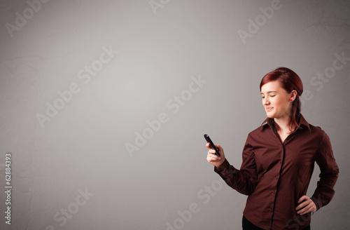 young lady standing and holding a phone with copy space