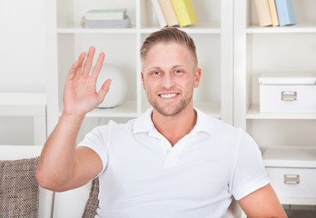 Businessman waving in pleasure to his laptop