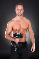 Athletic muscular man lifting weights