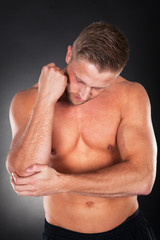 Fit young man with an elbow injury