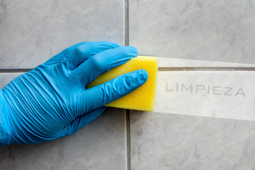 Sponge cleaning bathroom with spanish lettering