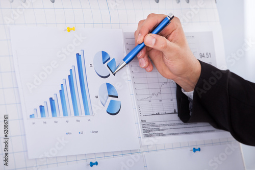 Businessman Analyzing Graph With Pen