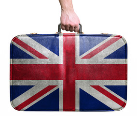Tourist hand holding vintage leather travel bag with flag of Gre