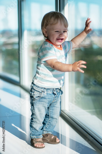Happy baby boy near big window