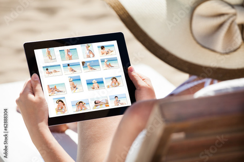 Woman Looking At Her Pictures On Digital Tablet
