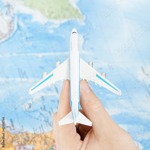 Toy aircraft in hand with map on background - 1 to 1 ratio