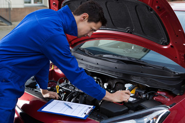 Mechanic In Uniform Repairing Car