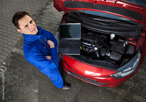 Mechanic With Arms Crossed Standing By Car