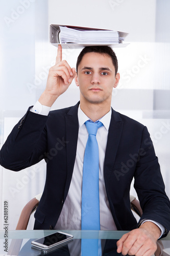 Businessman Balancing Binder With Finger