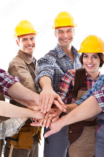 Diverse group of construction workers stacking hands