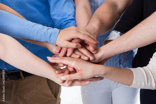 Group of people stacking hands together