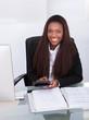 Confident Businesswoman Calculating Tax At Desk