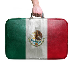 Tourist hand holding vintage leather travel bag with flag of Mex