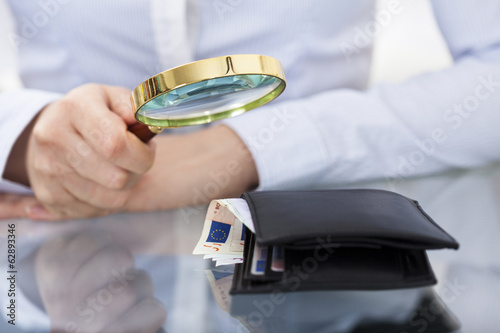 Businessperson With Magnifier And Wallet