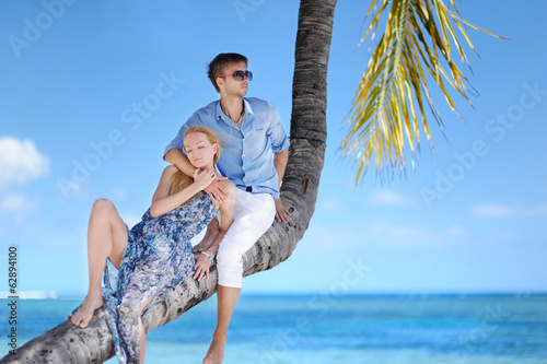 Beautiful young couple sitting on palm tree