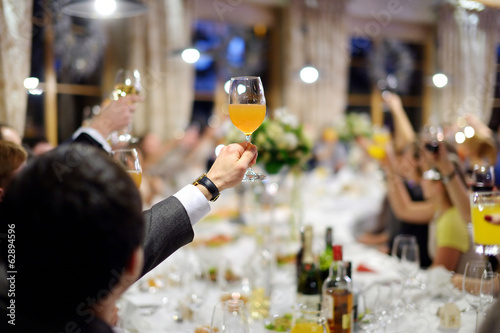 Men's hand holding glass of juice